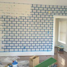 A woman tapes up her living room wall. Her faux brick idea? Get ready to gasp!