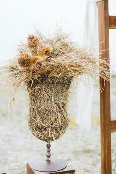 Idea for rustic wedding in a farmhouse. Iron vase filled with straw and dried flowers