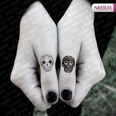 black and white fingers skulls tattoo