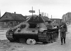 German military photographer walking past blasted Russian tank, undated.