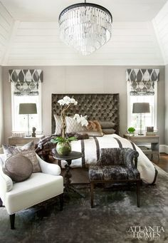 Interior designer Michel Boyd softened this texture-driven master bedroom's soaring ceiling with a jewel-like Restoration Hardware chandelier and a commanding, oversize tufted headboard.