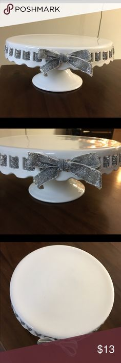 """Raised Ceramic Cake Plate Stand This is a beautiful raised cake stand. White ceramic. Pretty silver glittered bow entwined within. You can easily swap out the ribbon to a color of your choice. Scalloped edges. Used once for my wedding in 2015. No breaks and in perfect condition. Given to me as a gift in 2015 for my wedding shower. From HomeGoods. Hand wash. Made in China. 10"""" diameter and 4 1/2"""" tall. Base measures about 5 1/2"""". Other"""