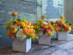 ranunculus, kermit poms, carnations, acacia in white ceramic cubes. yellow reception wedding flowers, wedding decor, wedding flower centerpiece, wedding flower arrangement, add pic source on comment and we will update it. www.myfloweraffair.com can create this beautiful wedding flower look.
