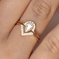 Wedding set: 0.3 carat pear diamond crown ring in 18k solid gold and a matching diamond V ring. Materials: 18k solid gold, 0.3 carat diamond, seven 1