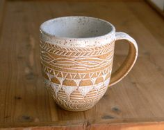 This lovely stoneware cup is ideal for your favorite hot drink. It is made in a wonderful tan clay with little speckles. The inside is glazed in a beautiful clean white, and the outside has been carved in a complex tribal inspired design, which is also white. The lip and handle of the mug are also glazed in white so they are pleasant to the touch. The rest of the clay has been left bare and natural. The clay has caused little flecks of dark brown to show through the white clay, in a…