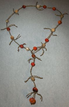 This unique jewellery piece is both a y-lariat necklace and a wrap bracelet. It is made with knotted linen with tiny antique french brass beads. It also contains red agate, rutilated crystal and carnelian. Its unique branches were inspired by nature and has a funky yet classy boho-chic design. This piece sparkles!