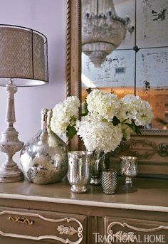 Hints of silver and mercury glass glitter on the antique sideboard - Traditional Home® / Photo: Colleen Duffley / Design: Paige Sumblin Schnell & Anna Kay Porch