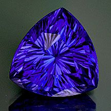 "Tanzanite Trillion ""Glow UC"" Concave Cut Weight: 6.92 cts Measurements: 11.9mm, depth 8.3mm Clarity: VVS Origin: Tanzania Enhancements: Heat only Description: Fabulous. Extremely saturated violet-blue, what Tanzanite is supposed to look like! Top color, big, clean and awesome concave-cutting. (Cut by Andrew Gulij) Pantone 2735/2746C"