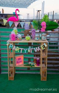 """Este candy bar (o mesa dulce) surgió con la temática tropical porque la fiesta de inauguración se hizo en una terraza en pleno verano, y ¿cómo no? tenía que llevar una piña pintada a mano, un flamenco, unas hojas del mismo estilo y unos banderines de colores a juego con la temática y el letrero de ¡""""Party time""""!"""