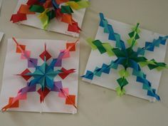 """Radial Relief Paper Design 3"""" squares: Fold the square in half and then on one side fold each corner separately toward the creased side. It looks similar to a paper airplane. Once the fold is created, holding the paper together tightly, the area where you put glue looks like a diamond with a line down the middle."""