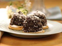 Mums-mums på mördegsbotten doppade i mörk choklad och kokos.