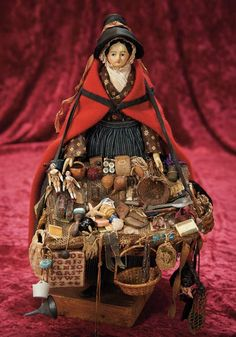 "Lot: Early German Papier-Mache Doll as Welsh Peddler Lady 11"" (25 cm.) Papier-mache shoulder head with sculpted black hair in chignon, painted facial features, blue eyes, painted brows and eyeliner, closed mouth, slender kid body with wooden lower limbs.  Comments: for the English trade with original German papier-mache doll, circa 1850."