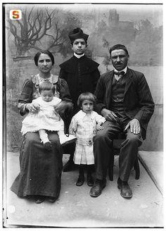Giulio Pili, Gruppo di famiglia in abiti borghesi, con chierico ripresi in posa in esterno con fondale dipinto