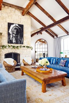 Ranch inspired living space with high ceilings, a stone fireplace, a denim sofa, and a leather bench