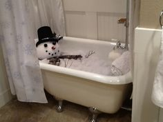 """This is my """"Bathtub Snowman"""".  I fell in ♥ w/this snowman :http://adebbie-dabblechristmas.blogspot.com/2010/11/sneak-peek-and-country-folks-tour-part.html and knew I had to have one of my own.  I filled the tub with unused blankets and quilts, topped it with a white mattress pad, added a """"frosted snow blanket"""" (aka quilt batting with sparkles).  The head is a syrafoam ball covered with same """"snow blanket"""".  Mouth = buttons.  Nose = corn cob.  Eyes = squashed table tennis balls painted black."""