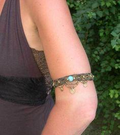 Ein handgeknüpftes Oberarmband mit einer großen Türkis Perle und kleinen Messingperlen und Messinganhänger aus hell- und dunkel olivfarbenem gewachsten Garn. Kann auch um den Fuß als Fußkettchen...