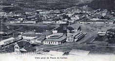 Cartão postal com imagem do centro de Poços de Caldas, onde hoje está a Praça Pedro Sanches. Em primeiro plano a Rua Junqueiras, na qual se observa o antigo Balneário e, junto à torre, o Passadiço Coberto que o ligava ao Hotel. 1909