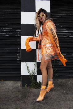 Orange grunge glam. Pair your favorite silver, heavy metal accessories with bright pops of color for a new age grunge and 90s style look. This clear raincoat and clear boot is totally on trend for 2017.    Follow us @VidaKush on Instagram, Facebook, and Tumblr to keep up with all our most recent creations and photoshoots!