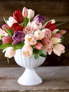 An arrangement of pretty tulips in a simple white vase makes a unique centerpiece. Find more centerpiece ideas: http://www.bhg.com/wedding/flowers/wedding-centerpiece-ideas/?socsrc=bhgpin062812#page=8