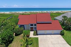 The crisp rectangles that inform the interior and exterior design of this beautiful home at 1290 Old Doubloon Drive, coupled with the warm crimson of the Mediterranean stone-coated steel roof, make this exceptional oceanfront home a standout.