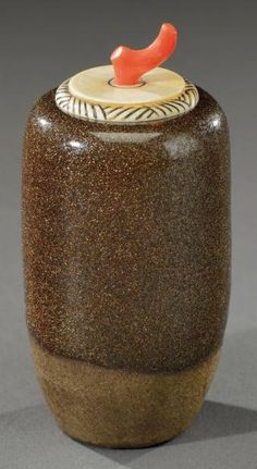 HENRI SIMMEN (1880-1963) et Yokohama O'KIN dite Eugénie Jubin (1880-1948)  A rare and exceptional brown enamelled stoneware vase with golden crystallizations, carved ivory stopper and red coral handle. Intaglio signature «HSim» and letters. Circa 1930. H: 4 in