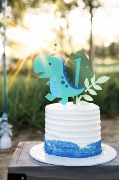 Dinosaur cake topper with a set of leaves and the age 1 in blue. Can be made in any color, and number stick can be any age you need.  Dinosaur measures 5 x 4 1/2 Leaves measures 5 1/4 x 4 1/2