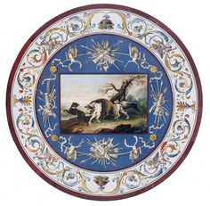 VERY FINE ITALIAN MICROMOSAIC TABLE TOP Second Quarter 19th Century. Of circular form, centered by a rectangular panel attributed to Aguatti, depicting hounds attacking a boar, surrounded by trophies, bucrania, and rosettes joined with ribbon on a blue ground, surrounded by griffins, urns and rinceaux on a white ground. Diameter 31 inches. Together with a Neoclassical style gilt-bronze base. Height 28 1/2 inches. Provenance: Collection of Gianni Versace.