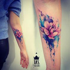 tatuaje flor de loto, tatuaje de acuarela en azul, morado y rosado, antebrazo mujer, flor de loto medio abierta
