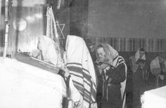Lodz, Poland, Men praying in a synagogue in the ghetto on Sukkot (a Jewish holiday), one of them is holding the traditional four species of plants.