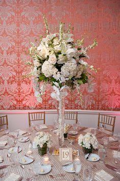 blanco, marfil, verde y pieza central floral en la mesa de recepción de estar cubierta con un mantel a rayas blanco y dorado con velas y pequeños arreglos florales blancos - foto de boda con sede en Houston fotógrafo Adam Nyholt