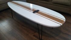 This surfboard coffee table has that classic old school look with realistic features and dimensions of a real surfboard. It is stained using a water based varnish with white stripes. Well be glad to color match if you have a certain color you want to use. The board is 60 inches Long by 19