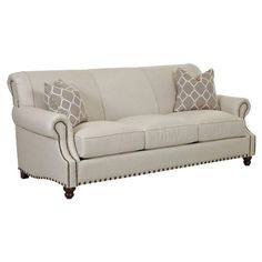 Showcasing nailhead trim and beige upholstery with welted details, this classic sofa brings traditional appeal to your living room or home library.