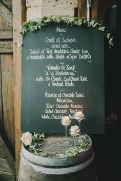 Chalkboard Menu sign of a wooden barrel with candles -  Image by Modern Vintage Weddings - Lusan Mandongus wedding dress, Jenny Packham headpiece & Jimmy Choo shoes at a destination wedding in a Chateau in France with groom in a Reiss suit