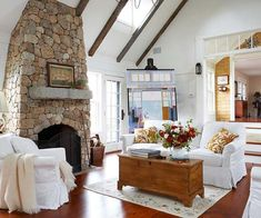 Old Meets New: White brings cohesion to a large room and its different layers of color and texture. In this bright and breezy living room, wide-plank pinewood floors and finishes emphasize the house's history, while the dark tones contrast with the contemporary white walls and slipcovered seating in an old-world/new-world combination.