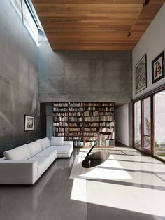 polished cement, warm natural light from high glass windows, richly hued wood boards on the ceiling, a cozy white sofa, and tall book shelves make this minimalist interior cozy and inviting