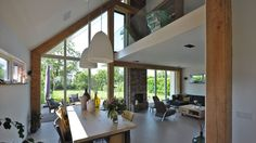 Living room and dining area with amazing two storey windows : by Bongers Architecten