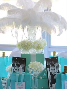 Set the right tone for any feminine soiree with a Breakfast at Tiffany's theme. Cut holes in standard gift boxes, place a vase filled with clear glass pebbles in the middle and wrap the boxes in blue wrapping paper to resemble Tiffany & Co. boxes. Hydrangea-filled vases and martini glasses and black-and-white photos of Audrey Hepburn complete the feminine look. Add Breakfast at Tiffany's movie quotes to Tiffany-blue gift bags to collaborate with the theme.
