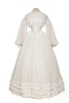 Robe de mariée, corsage, jupe, jupon, ceinture  Création :   France  1862, Second Empire  Matières et techniques :   Mousseline de coton, baleine de métal dans la ceinture