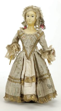 """Queen Anne Doll  England, mid 18th century, wooden shoulder head with long neck and graceful features, brown pupilless glass eyes, platinum curled wig, kid body with wooden limbs, appropriately redressed in antique satin and brocade  Size: 17"""" t. $1,000 starting bid"""