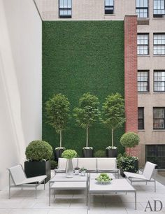 On a New York townhouse's terrace,  a wall blanketed in faux boxwood offsets outdoor furniture by Richard Schultz and limestone paving.