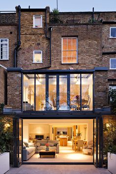 two storey glass extension attached to terraced house by aprops