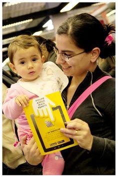 Ester, de dois anos, no colo da mãe, Noemi Godoy, com o folheto do aplicativo SP Serviços, que facilita agendamento no Poupatempo. Ela foi ao Poupatempo Guarulhos em junho de 2015)