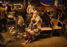Muslim woman waiting at a food stall / New Dehli // India /// Kevin Frayer
