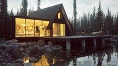 Красивый домик на берегу озера в лесу с небольшой панорамной пристройкой