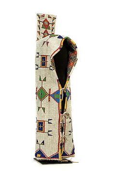 Sioux beaded hide cradle -  Sinew-sewn and fully beaded using bead colors of red white-heart, dark blue, pea green, greasy yellow, and white; with large beaded rawhide tab on hood; lined with plaid polished cotton; hide thong closures, length 25.25 in. fourth quarter 19th century