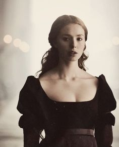Black velvet; Juliet sleeves, an empire waist, and a low, wide neck.