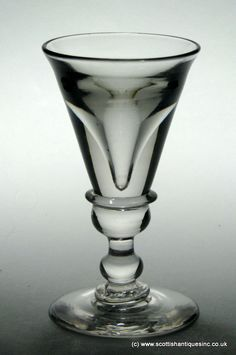 A Georgian Deceptive Toastmasters wine glass which dates to 1730.  It has a deceptive bowl above a shoulder knop and plain stem above a conical folded foot.   http://scottishantiques.com/georgian-glass/plain-stems/deceptive-toastmaster#.VjKLcsbX5TN
