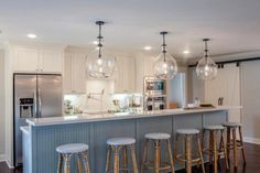 Bright Blue and White Kitchen With White Barn Doors, Large Island and Wicker Bar Stools