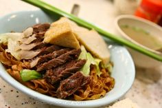 Beef brisket with fish cake on thick noodles -slightly rough flat noodles in soya based sauce with beef and fish cakes