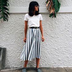 T-shirt branca com saia de listras, cinto e tênis